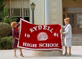Principal Mrs. McGee raising school flag with assistant Blanche