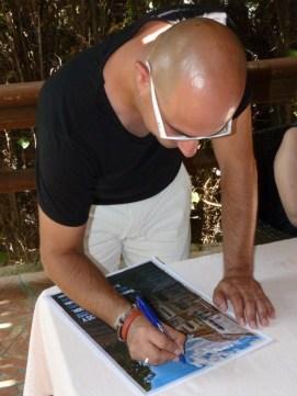 Jaime Helios firmando uno de los carteles